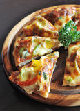 Vegetarian pizza. Slice of vegetarian pizza on wooden board Royalty Free Stock Photo