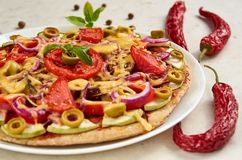 Vegetarian pizza with tomatoes, bell pepper, onion, green olives, cheese and spices on white background close up Stock Image
