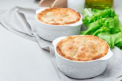 Vegetarian pot pie with lentil, mushrooms, potato, carrot and green peas, covered with puff pastry, in baking dish, horizontal,. Vegetarian pot pie with lentil royalty free stock image
