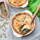 Vegetarian pot pie with lentil, mushrooms, potato, carrot and green peas, covered with puff pastry, in a baking dish, square, top. Vegetarian pot pie with lentil royalty free stock photo