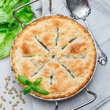 Vegetarian pot pie with lentil, mushrooms, potato, carrot and green peas, covered with puff pastry, in baking dish, top view,. Vegetarian pot pie with lentil royalty free stock photos