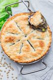 Vegetarian pot pie with lentil, mushrooms, potato, carrot and green peas, covered with puff pastry, in baking dish, vertical, top. Vegetarian pot pie with lentil royalty free stock photo