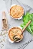 Vegetarian pot pie with lentil, mushrooms, potato, carrot and green peas, covered with puff pastry, in baking dish, vertical, top. Vegetarian pot pie with lentil royalty free stock images