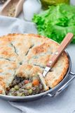 Vegetarian pot pie with lentil, mushrooms, potato, carrot and green peas, covered with puff pastry, in a baking dish, vertical. Vegetarian pot pie with lentil royalty free stock images