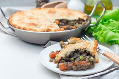 Vegetarian pot pie with lentil, mushrooms, potato, carrot and green peas, covered with puff pastry, on white plate, horizontal,. Vegetarian pot pie with lentil royalty free stock photos