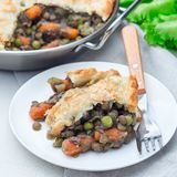 Vegetarian pot pie with lentil, mushrooms, potato, carrot and green peas, covered with puff pastry, on white plate, square. Vegetarian pot pie with lentil stock photos