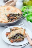 Vegetarian pot pie with lentil, mushrooms, potato, carrot and green peas, covered with puff pastry, on white plate, vertical. Vegetarian pot pie with lentil royalty free stock images