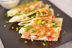 Vegetarian quesadilla. With sour cream. Selective focus on the front wedge stock image