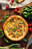 Vegetarian quiche with cherry tomatoes and green asparagus Stock Photography