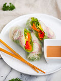 Vegetarian roll. With sauce. Vegetables and fresh herbs in a rice paper. Chinese chopsticks for decoration Royalty Free Stock Photo