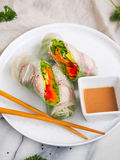 Vegetarian roll. With sauce. Vegetables and fresh herbs in a rice paper. Chinese chopsticks for decoration Royalty Free Stock Image