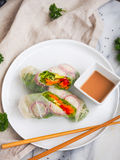 Vegetarian roll. With sauce. Vegetables and fresh herbs in a rice paper. Chinese chopsticks for decoration Royalty Free Stock Photos