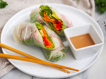 Vegetarian roll. With sauce. Vegetables and fresh herbs in a rice paper. Chinese chopsticks for decoration Stock Images
