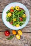 Vegetarian salad with arugula, kumquats and tomatoes Stock Images
