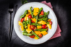 Vegetarian salad with asparagus, cherry tomatoes, bell pepper, slate background Stock Images