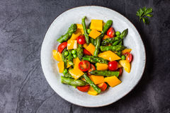 Vegetarian salad with asparagus, cherry tomatoes, bell pepper, slate background Royalty Free Stock Photo