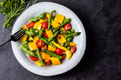 Vegetarian salad with asparagus, cherry tomatoes, bell pepper, slate background Royalty Free Stock Photos