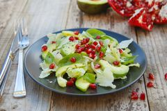 Vegetarian salad with avocado, greens, leaves, pomegranate and letuce leaves. Wooden rustic table. royalty free stock photo
