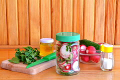 Vegetarian salad in a glass jar. Salad with fresh cucumbers and radishes. Trends in healthy eating. Set for cooking salad Stock Images