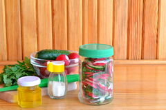 Vegetarian salad in a glass jar. Salad with fresh cucumbers and radishes. Trends in healthy eating. Set for cooking salad Royalty Free Stock Photography