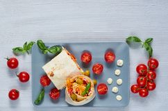 Vegetarian sandwich or lavash with fresh vegetables, sauce on the gray plate decotated with cherry tomatoes, basil leaves. Traditional Iranian or Indian food Royalty Free Stock Image