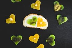 Vegetarian sandwich with sugar cream, citrus with kiwi fruit on black table. Flat lay, top view. Vegetarian sandwich with sugar cream, citrus with kiwi fruit on Royalty Free Stock Photography