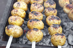 Vegetarian skewers on the grill. Vegetarian skewers made from potatoes and mushrooms on the grill outdoors Royalty Free Stock Photos