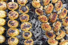 Vegetarian skewers on the grill. Vegetarian skewers made from potatoes and mushrooms on the grill outdoors Stock Photo