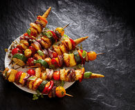 Vegetarian skewers with halloumi cheese and mixed vegetables on black background stock image