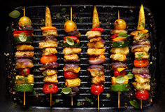 Vegetarian skewers with halloumi cheese and mixed vegetables on black background stock photography