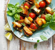 Vegetarian skewers with halloumi cheese and vegetables. Grilled skewers of halloumi cheese and vegetables with addition aromatic herbs, top view Royalty Free Stock Image