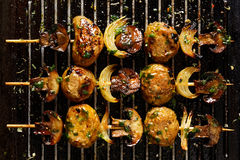 Vegetarian skewers with potatoes, mushrooms and onions in a herb dressing on grill pan Royalty Free Stock Images