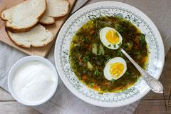 Vegetarian sorrel soup with egg, served with sour cream and bread. Rustic style. Vegetarian sorrel soup with egg, served with sour cream and bread. Rustic style stock photo
