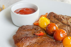 Vegetarian steak made from vegan meat seitan, with cherry tomatoes Stock Images