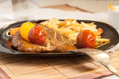 Vegetarian steak from vegan meat seitan, cherry tomatoes and fries Royalty Free Stock Image