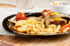 Vegetarian steak from vegan meat seitan, cherry tomatoes and fries Stock Photography