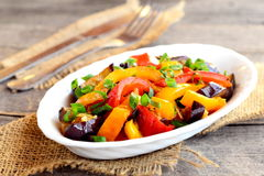 Vegetarian stew on a plate and on wooden table. Steamed aubergine, red and orange peppers and green onions. Diet dish Royalty Free Stock Photos