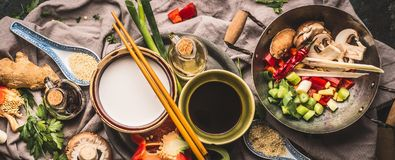 Vegetarian stir fry ingredients: chopped vegetables, spices,coconut milk, soy sauce,,wok and chopsticks, top view, banner. Asian f Stock Photo