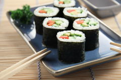 Vegetarian Sushi. Rolls on a blue plate stock images