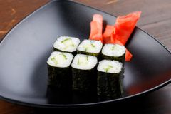 Set sushi rolls with ginger on a black plate on a dark wooden background. royalty free stock photography