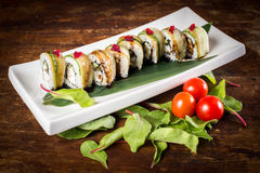 Vegetarian sushi roll. With tomatoes on wooden table Royalty Free Stock Image
