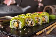 Vegetarian sushi rolls avocado with cream Philadelphia cheese, sesame, unagi sauce. royalty free stock photo