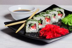 Vegetarian sushi rolls on a black square plate with wasabi, soy sauce and ginger. White wooden background.  royalty free stock image
