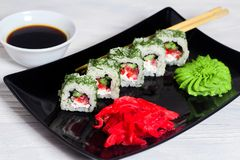 Vegetarian sushi rolls on a black square plate with wasabi, soy sauce and ginger. White wooden background.  stock image