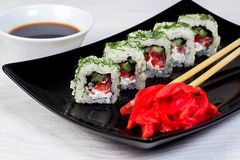 Vegetarian sushi rolls on a black square plate with wasabi, soy sauce and ginger. White wooden background.  stock photos