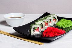 Vegetarian sushi rolls on a black square plate with wasabi, soy sauce and ginger. White wooden background.  stock images