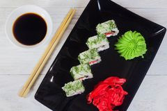 Vegetarian sushi rolls on a black square plate with wasabi, soy sauce and ginger. White wooden background.  stock photo
