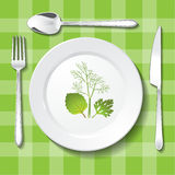Vegetarian table appointments on green tablecloth. Stock Photos