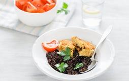 Vegetarian table. Black quinoa, oatmeal cutlets, tomato salad, l. Plate with black quinoa and oatmeal cutlets with prunes on white wooden table with tomato salad stock photo