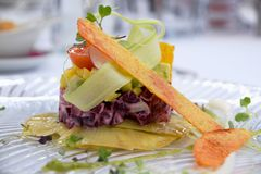 Vegetarian dish with beetroot, corn, avocado, tomatoes and root vegetables. Fine dining and gourmet vegetarian meal on a glass plate in a restaurant. Ingredients stock photography